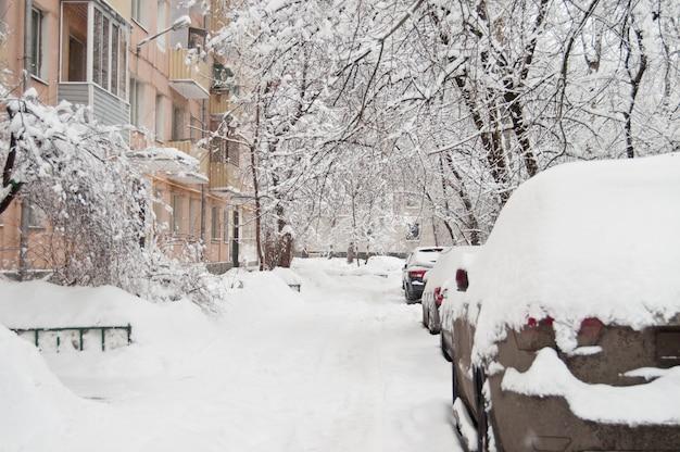 A queda de neve mais forte. carros cobertos de neve no quintal. Foto Premium