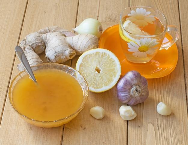 A raiz de gengibre e mel na mesa de madeira. Foto Premium