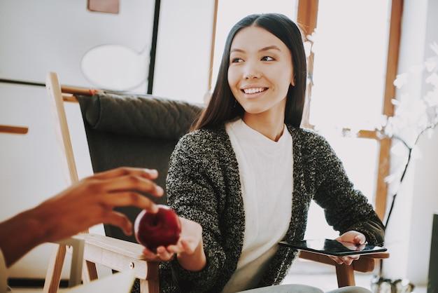 A rapariga no escritório dá a apple ao colega Foto Premium