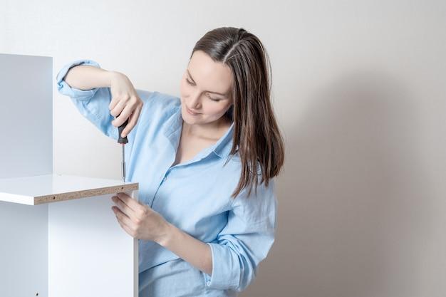 A rapariga recolhe a mobília com uma chave de fenda, espaço da cópia. Foto Premium