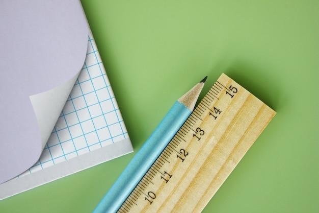 A régua e o lápis de madeira estão perto do caderno da escola em um fundo verde. Foto Premium