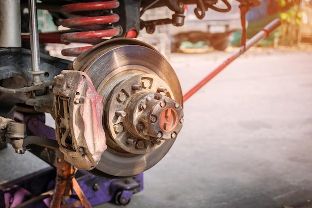 A roda dianteira do carro foi removida para consertar o sistema de freio. Foto Premium