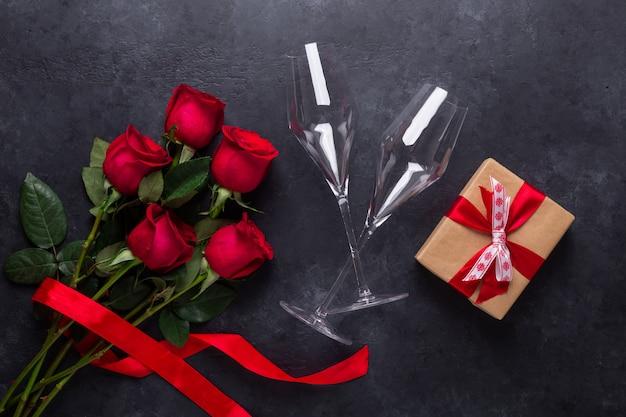 A rosa do vermelho floresce o ramalhete, caixa de presente, vidros do champanhe na pedra preta. dia dos namorados Foto Premium
