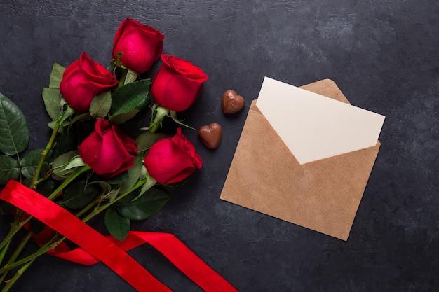 A rosa do vermelho floresce o ramalhete, envelope, doces do chocolate na pedra preta. cartão de dia dos namorados Foto Premium