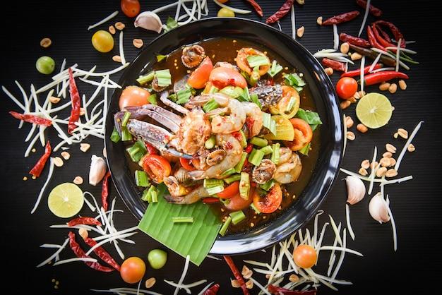 A salada do marisco picante com os berbigões frescos do caranguejo do camarão serviu em ervas e em especiarias dos legumes frescos da placa preta ingredientes. Foto Premium