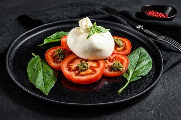 A salada do queijo e dos tomates de burrata serviu na placa preta. fundo escuro. vista do topo Foto Premium
