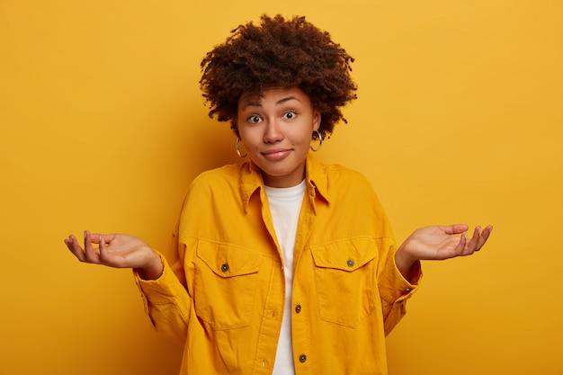A senhora africana encolhe os ombros e expressa incerteza, toma decisões, veste roupas da moda, estende as palmas das mãos para os lados isoladas na parede amarela. Foto gratuita