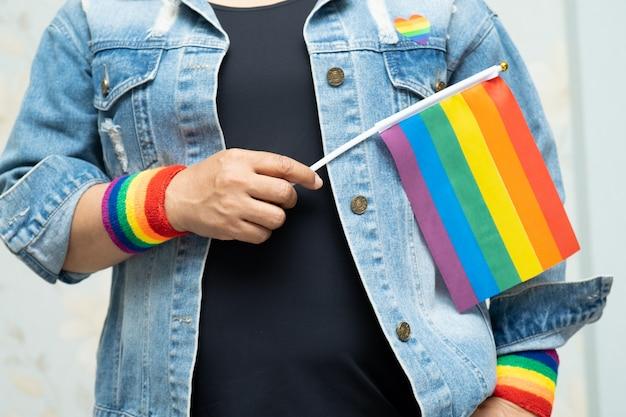 A senhora asiática que guarda a bandeira da cor do arco-íris, símbolo do mês do orgulho de lgbt comemora anual em junho. Foto Premium