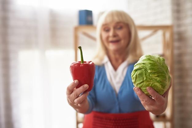 A senhora caseiro dos ingredientes da salada oferece vegetais. Foto Premium