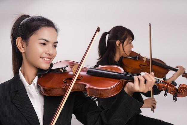 A senhora com violino está tocando música na frente da senhora está jogando viola Foto Premium