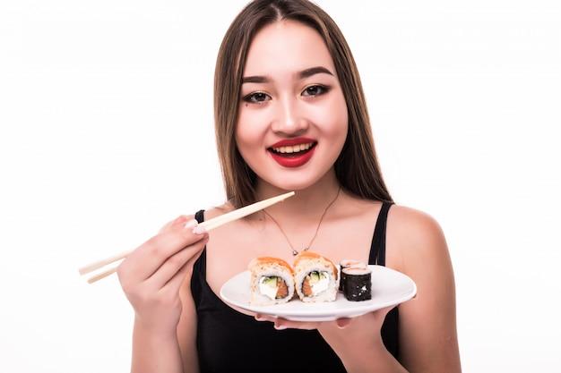A senhora sorridente com cabelos pretos e lábios vermelhos prova suushi rolls com pauzinhos de madeira na mão Foto gratuita