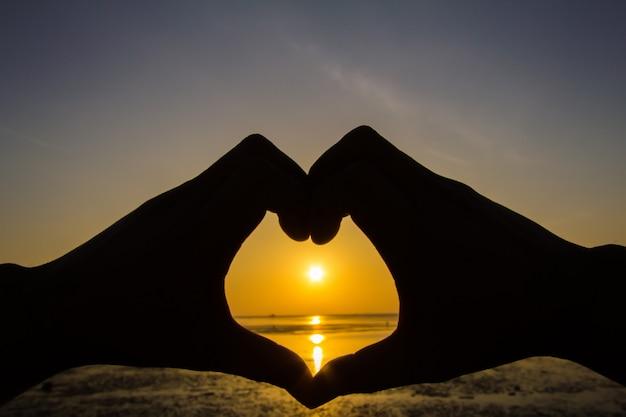 A silhueta da mão de um homem em um belo nascer do sol captura o sol no coração. Foto Premium
