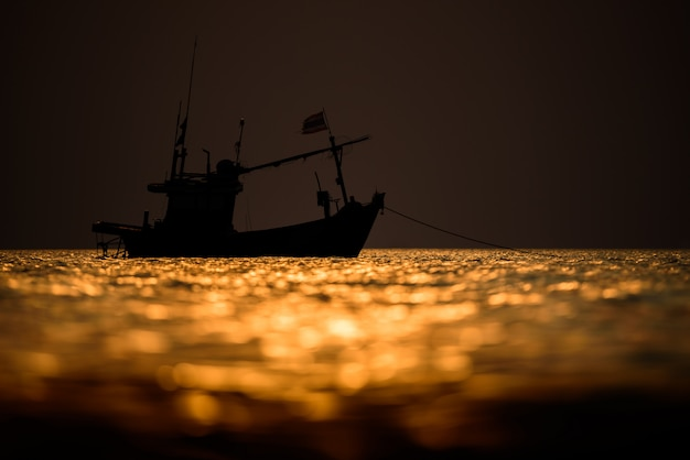 A silhueta de barco de pescador no mar com o céu do sol Foto Premium
