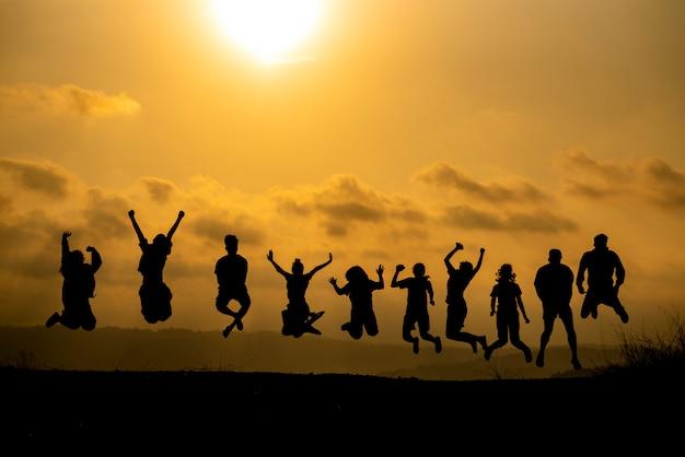 A silhueta de um grupo de pessoas está comemorando o sucesso no topo da colina. Foto Premium