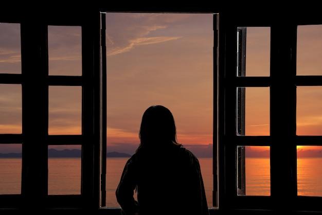 A silhueta de uma jovem mulher olhando por do sol a janela com vista para o mar. Foto Premium