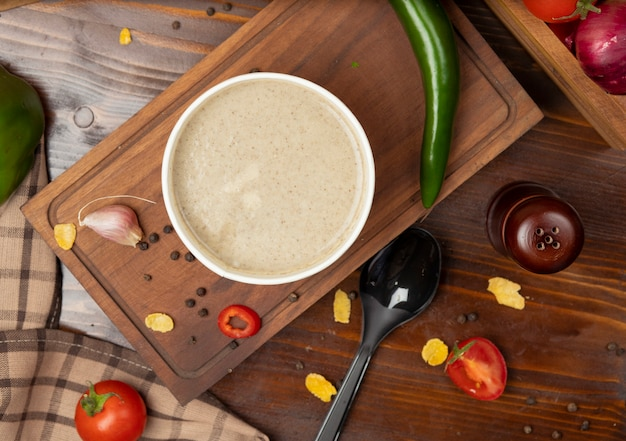 A sopa de cogumelo de creme na bacia descartável do copo serviu com vegetais verdes. Foto gratuita