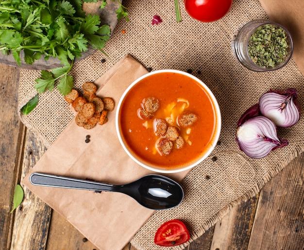 A sopa do tomate com biscoitos e queijo do pão na bacia descartável do copo serviu com vegetais verdes. Foto gratuita