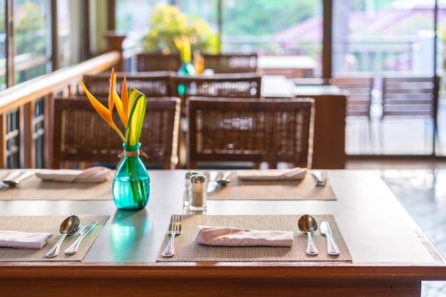 A tabela de madeira ajustou-se para a refeição no restaurante com interior acolhedor, tempo de café da manhã. Foto Premium
