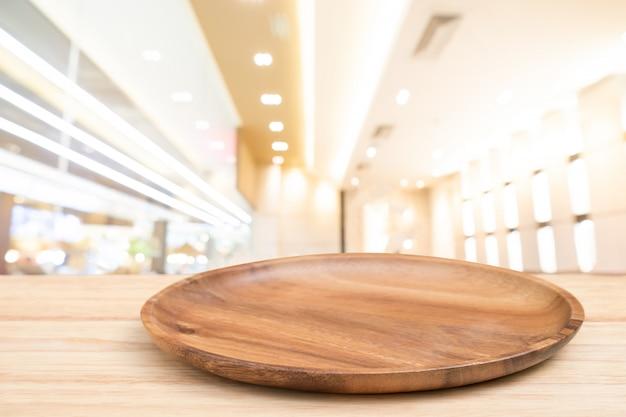 A tabela de madeira da perspectiva e a bandeja de madeira na parte superior sobre o backgrounk claro do bokeh do borrão podem ser nós Foto Premium