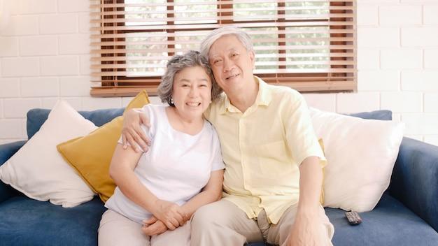 A televisão de observação dos pares idosos asiáticos na sala de visitas em casa, par doce aprecia o momento do amor ao encontrar-se no sofá quando relaxado em casa. Foto gratuita