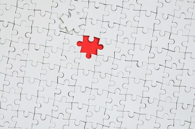 A textura de um quebra-cabeça branco em um estado montado com um elemento em falta, formando um espaço vermelho Foto Premium