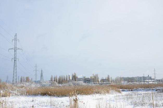 A torre de linha de energia está localizada em uma área pantanosa, coberta de neve Foto Premium