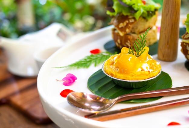 A torta de manga mini é servida em um prato branco e adornada com lindas flores. Foto Premium