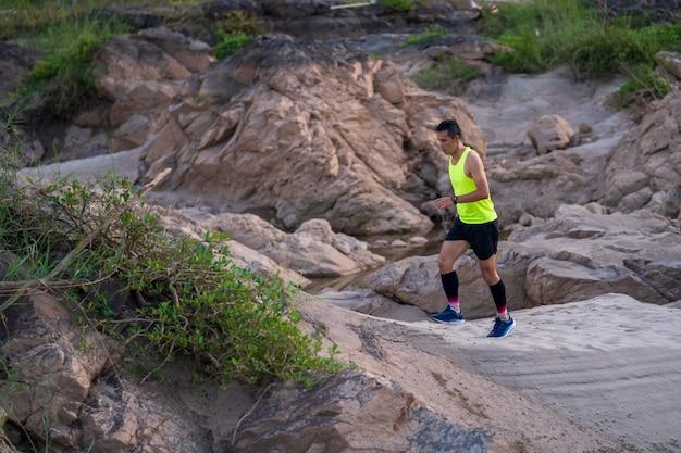 A trilha de atleta correndo na montanha de pedra Foto Premium