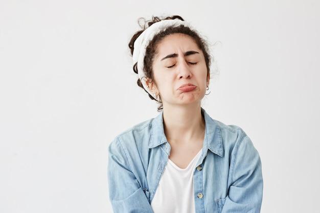 A triste e triste mulher triste com cabelos escuros e ondulados parece ofendida, faz beicinho nos lábios, franze a testa em desespero, frustrada, depois de receber más notícias. jovem infeliz na camisa jeans chora de frustração Foto gratuita
