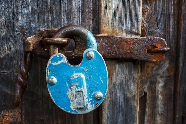 A velha fechadura azul enferrujada está fechada na porta da porta. Foto Premium