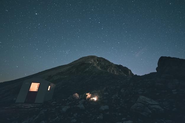 A via láctea sobre as montanhas, longa exposição sobre os alpes italianos-franceses, cabana de montanha e refúgio iluminado. imagem tonificada, filtro vintage, dividir a tonificação. Foto Premium
