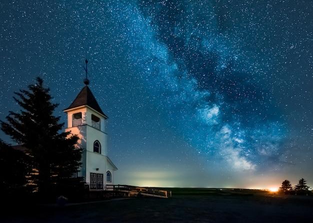 A via láctea sobre uma igreja luterana histórica nas pradarias de saskatchewan, canadá Foto Premium