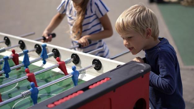 A vida moderna em uma cidade grande - as crianças jogam hóquei de mesa na rua Foto Premium