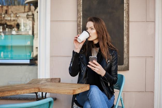 A vida selvagem na cidade consome muita energia. atraente pensativa e elegante turista feminina, sentado no pátio do café e tomando café Foto gratuita