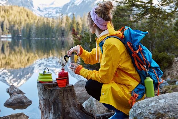 A visão externa de uma jovem usa equipamento turístico para fazer café e tem um fogão a gás portátil no toco Foto gratuita
