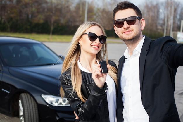 A visita bem sucedida à concessionária. casal jovem feliz escolhe e comprar um carro novo para a família Foto Premium