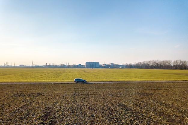A vista aérea da condução de carro pela estrada à terra reta através dos campos verdes no céu azul ensolarado copia o fundo do espaço. fotografia de zangão. Foto Premium