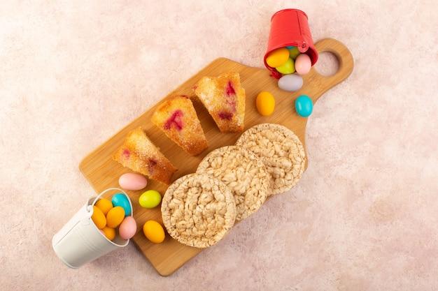 A vista de cima fatias de bolo de cereja com doces e biscoitos no bolo de mesa rosa brilhante biscoito açúcar Foto gratuita