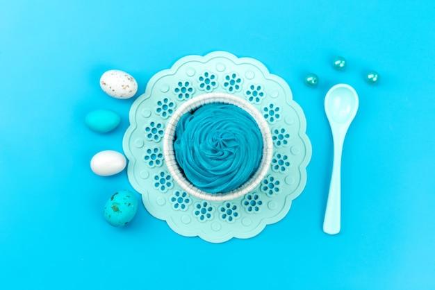 A vista de cima ovos e sobremesa azul e branco, com branco, colher isolada em azul, cor de comida Foto gratuita