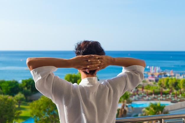 A vista de trás uma mulher em pé na varanda. manhã de verão. Foto Premium