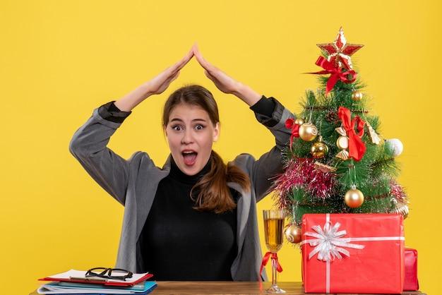 A vista frontal surpreendeu a garota sentada na mesa de mãos dadas como uma casa no telhado perto da árvore de natal e coquetel de presentes Foto gratuita