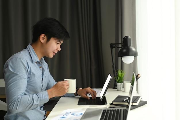 A vista lateral de um designer gráfico está trabalhando com o tablet do computador e tomando café em seu espaço de trabalho pela manhã. Foto Premium