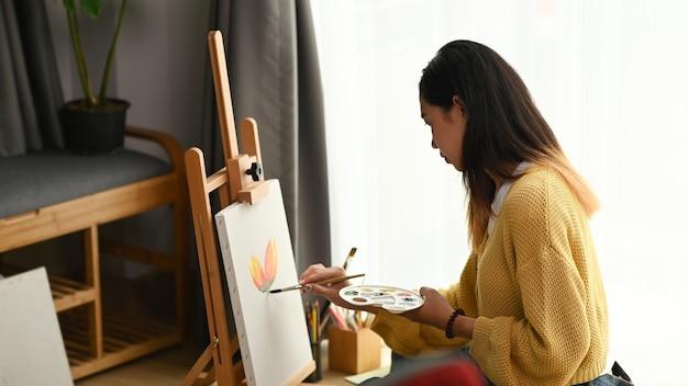 A vista lateral de uma pintora está fazendo um desenho com tinta de pôster em seu espaço de trabalho. Foto Premium