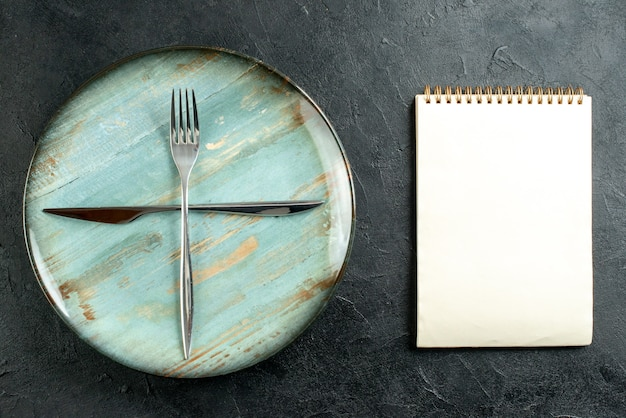 A vista superior cruzou o garfo e a faca no caderno de placa redonda ciano na mesa escura Foto gratuita