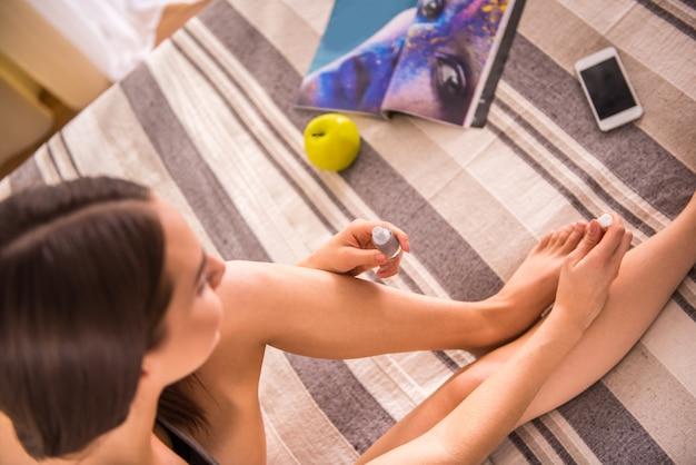 A vista superior da mulher está envernizando seus toenails em casa. Foto Premium