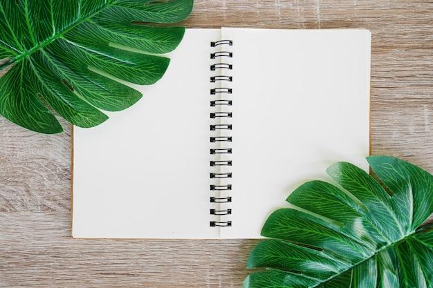 A vista superior do caderno aberto da placa no fundo de madeira da mesa com o monstera tropical verde sae. Foto Premium
