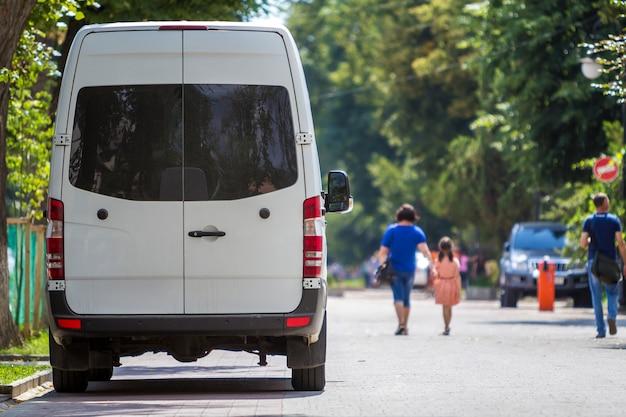 A vista traseira do passageiro branco tamanho médio van de microônibus de luxo comercial estacionou na rua da cidade de verão. Foto Premium