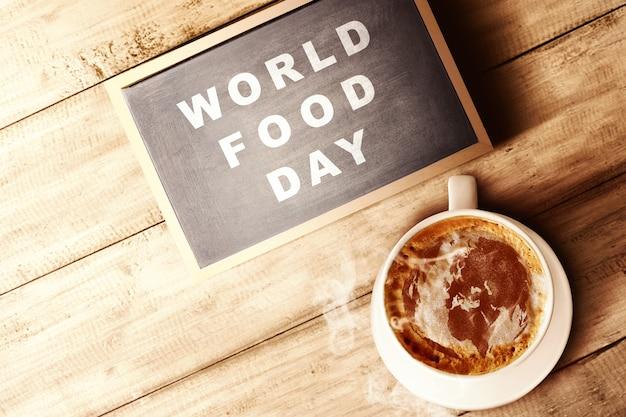 A xícara de café e lousa com texto dia mundial da comida na madeira Foto Premium