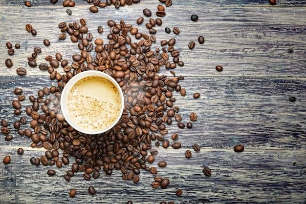 A xícara de café quente com grãos de café Foto Premium