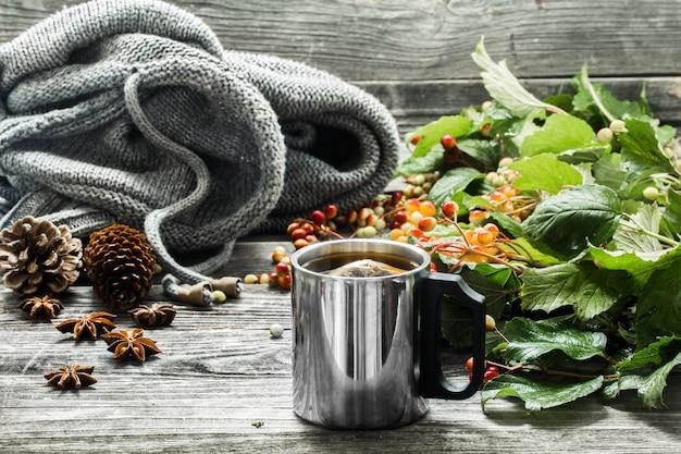 A xícara de chá em um fundo bonito de madeira com blusa de inverno, frutas, outono Foto gratuita